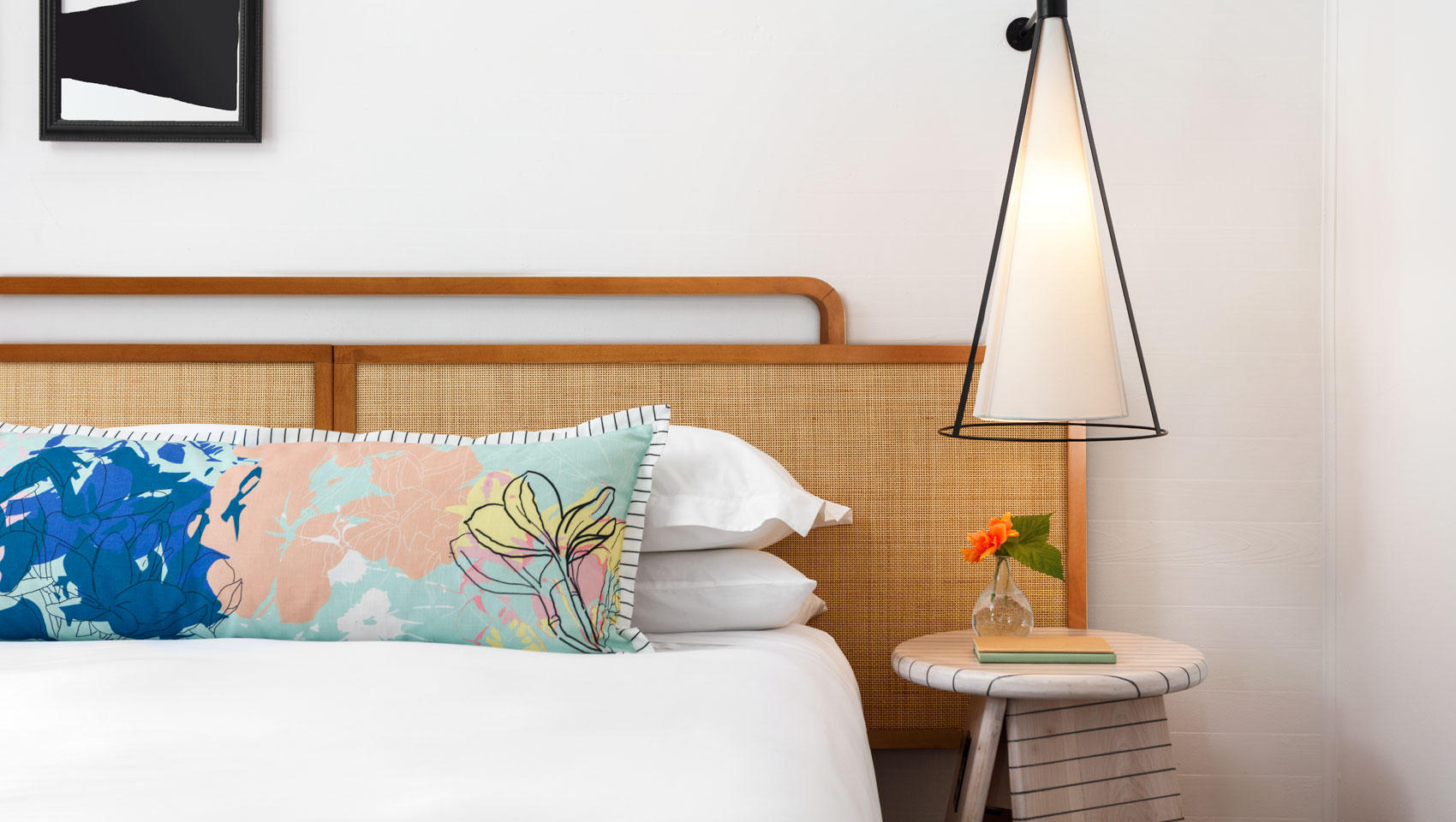 close up of king bed with orange flowers on the bedside table and modern lighting.