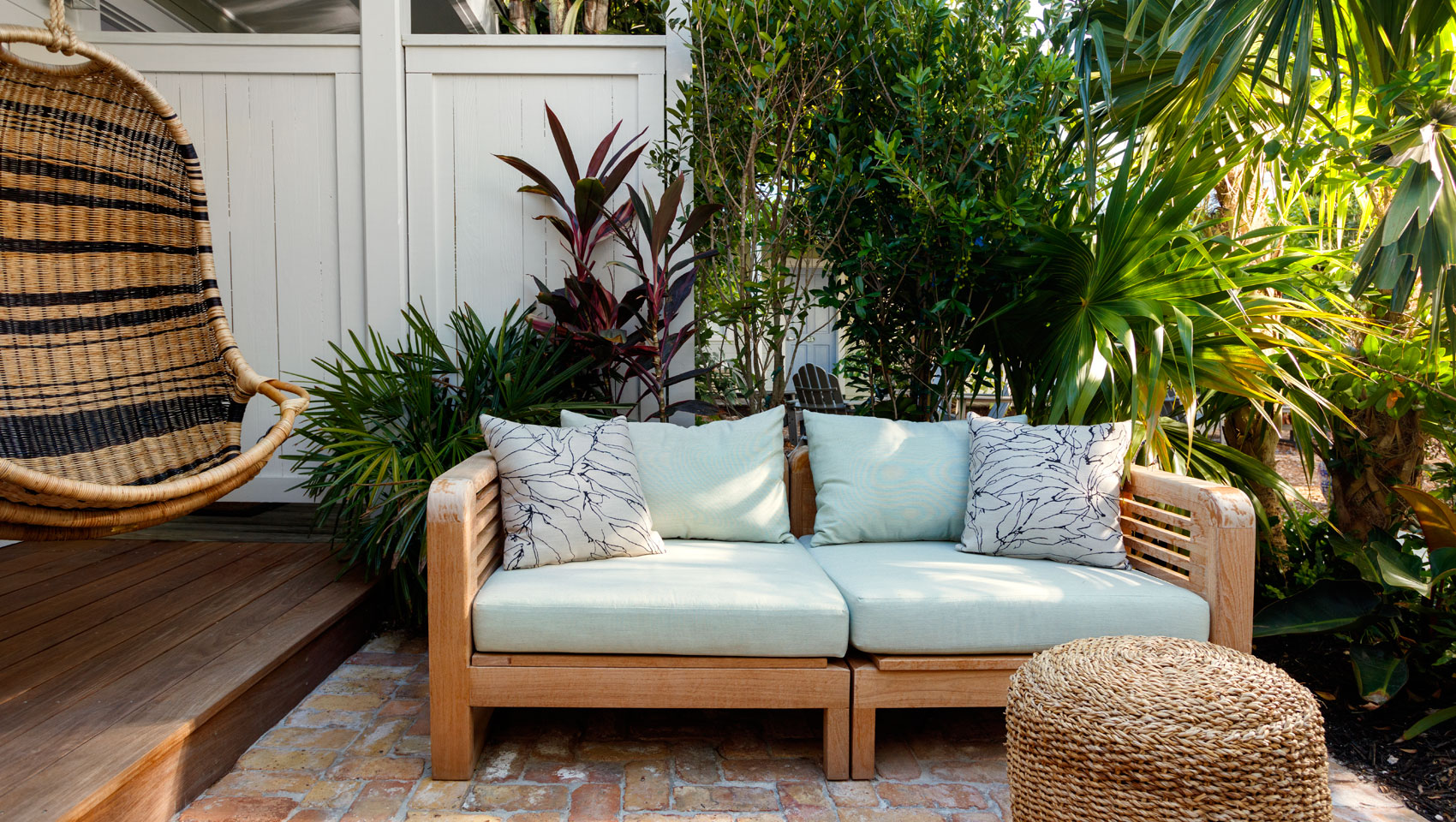 outdoor personal patio with wood couch and a white door.