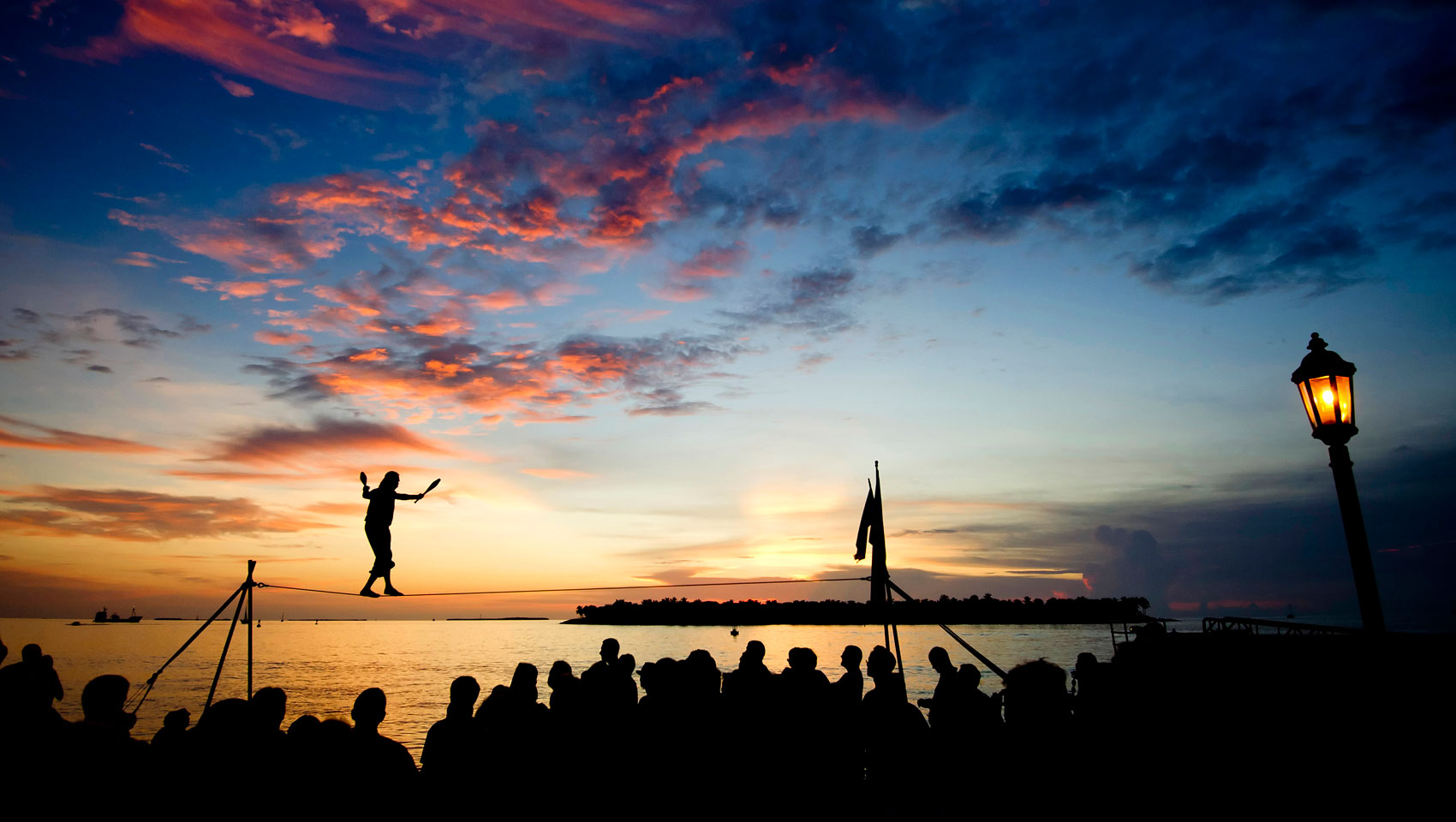 sunset event at mallory square with street performers and a crowd watching.