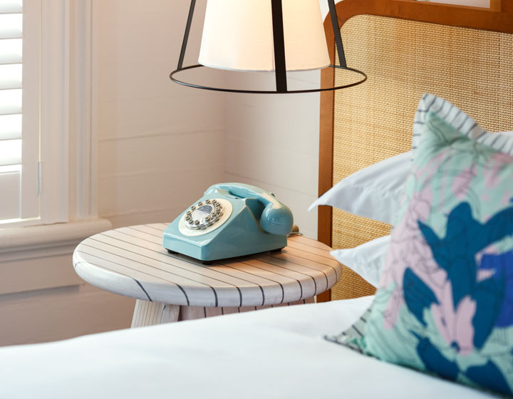close up of a king bed with white sheets, a pastel accent pillow and antique guestroom phone