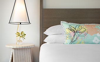 queen bed with pastel accent pillow and a bedside table with flowers and modern lighting