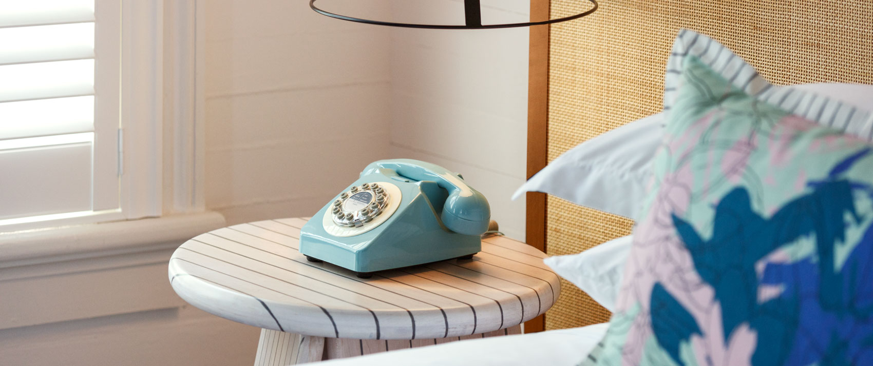 ridley house guestroom bed with a teal vintage telephone